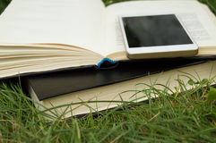 Libros, smartphone en un fondo de la hierba verde, concepto de educación y formación Imagen de archivo libre de regalías