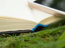 Libros, smartphone en un fondo de la hierba verde, concepto de educación y formación Fotografía de archivo
