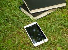 Libros, smartphone en un fondo de la hierba verde, concepto de educación y formación Foto de archivo libre de regalías