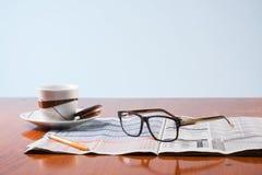 Libros, vidrios y café co de la taza en una tabla de madera Foto de archivo