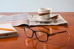 Libros, vidrios y café co de la taza en una tabla de madera Fotografía de archivo