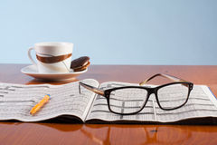 Libros, vidrios y taza de café en una tabla de madera Foto de archivo libre de regalías