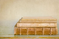 Libros viejos antiguos en un vector de madera Imagen de archivo libre de regalías