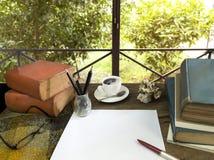 Libros viejos con el tratado, los vidrios y el lápiz en una tabla de madera adentro Imagen de archivo libre de regalías