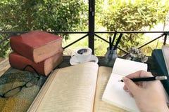 Libros viejos con el tratado, los vidrios y el lápiz en una tabla de madera adentro Foto de archivo