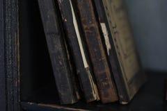 Libros viejos en el estante Libros viejos con los atascamientos del vintage y las cubiertas de libro de cuero doradas hermosas fotografía de archivo