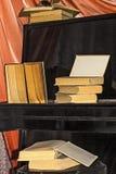 Libros viejos puestos en el piano Fotos de archivo libres de regalías