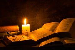 Libros viejos que son leídos por la luz de la vela fotografía de archivo libre de regalías