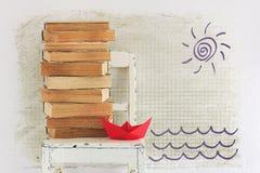 Libros viejos, silla y barco de papel rojo Imagen de archivo libre de regalías