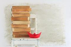 Libros viejos, silla y barco de papel rojo Foto de archivo