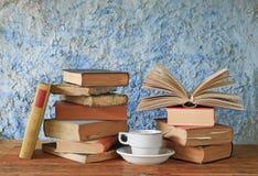Libros viejos, uno abierto y una taza de café Foto de archivo libre de regalías