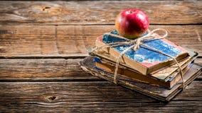 Libros viejos y manzana en el escritorio de la escuela Fotos de archivo libres de regalías