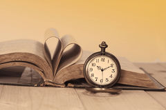 Libros viejos y relojes de bolsillo en el escritorio Imagen de archivo libre de regalías
