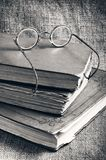 Libros viejos y vidrios en un fondo del yute Foto de archivo libre de regalías