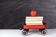 Libros y Apple del carro Foto de archivo