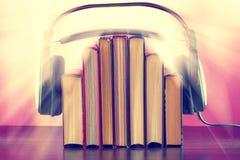 Libros y auriculares como concepto del audiolibro en una tabla de madera fotografía de archivo libre de regalías