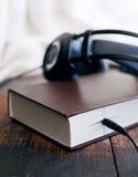 Libros y auriculares en grunge superficial de madera Imagenes de archivo