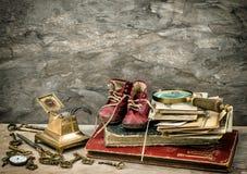 Libros y fotos antiguos, escribiendo los accesorios y los zapatos de bebé viejos Fotos de archivo libres de regalías