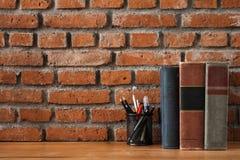 Libros y fuentes inmóviles en la tabla de madera con vagos de la pared de ladrillo Imágenes de archivo libres de regalías