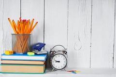 Libros y herramientas de la escuela en un estante de madera Fotos de archivo libres de regalías