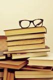 Libros y lentes en una maleta vieja, con un efecto retro foto de archivo