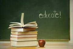Libros y manzana de escuela en el escritorio Fotografía de archivo libre de regalías