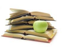 Libros y manzana en el fondo blanco Fotos de archivo