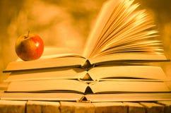 Libros y manzana en fondo de oro Foto de archivo libre de regalías