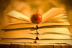 Libros y manzana en fondo de oro Fotografía de archivo