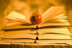 Libros y manzana en fondo de oro Imagen de archivo libre de regalías