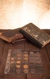 Libros y monedas del vintage en la tabla de madera vieja Foto de archivo libre de regalías