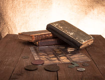 Libros y monedas del vintage en la tabla de madera vieja Imagen de archivo