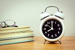 Libros y reloj Foto de archivo