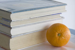 Libros y una naranja. Foto de archivo