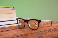 Libros y vidrios en una tabla de madera Fotos de archivo