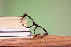 Libros y vidrios en una tabla de madera Fotografía de archivo