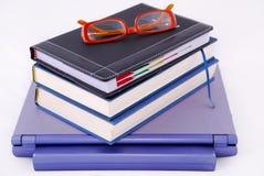 Libros y vidrios encima de la computadora portátil Fotografía de archivo