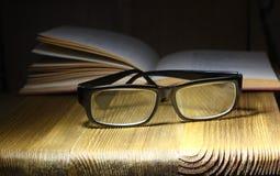 Libros y vidrios retros del estilo del foco suave en un fondo oscuro El concepto de lectura y de educaci?n imagen de archivo