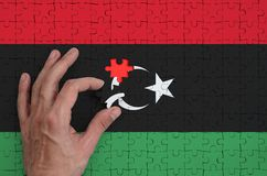 Libya flag is depicted on a puzzle, which the man`s hand completes to fold.  royalty free illustration