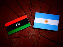 Libyan flag with Argentinian flag on a tree stump  Royalty Free Stock Photos