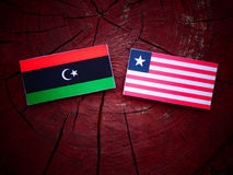 Libyan flag with Liberian flag on a tree stump isolated. Libyan flag with Liberian flag on a tree stump Royalty Free Stock Photography