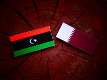 Libyan flag with Qatari flag on a tree stump isolated. Libyan flag with Qatari flag on a tree stump Royalty Free Stock Images
