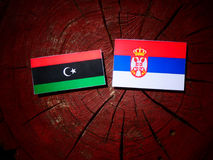 Libyan flag with Serbian flag on a tree stump isolated. Libyan flag with Serbian flag on a tree stump stock images