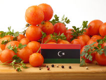 Libysche Flagge auf einer Holzverkleidung mit den Tomaten lokalisiert auf einem Weiß Lizenzfreies Stockbild