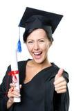 Licenciado de escuela con los pulgares del diploma para arriba Fotografía de archivo