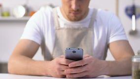 Licenciado no avental que datilografa no smartphone, procurando a receita para preparar o jantar vídeos de arquivo
