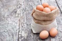 Licenzi la borsa con le uova sulla vecchia tavola Immagini Stock