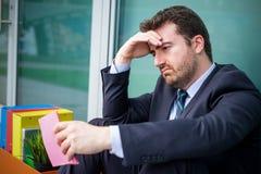 Licenziamento della lettura dell'uomo d'affari dopo la cessazione di impiego Fotografia Stock