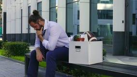 Licenziamento e assunzione Un impiegato turbato si siede su un banco ad un centro di affari con una scatola di cortona e gli ogge video d archivio