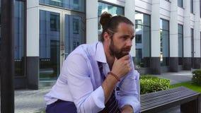 Licenziamento e assunzione Un impiegato turbato si siede su un banco ad un centro di affari con una scatola di cortona e gli ogge stock footage